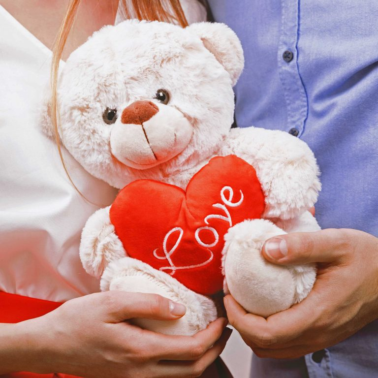 ตุ๊กตาหมีวันวาเลนไทน์ในมือของคู่รัก