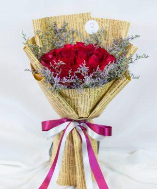 ช่อดอกกุหลาบแดง ห่อด้วยกระดาษสีน้ำตาลคลาสสิค ผูกริบบิ้นสีขาวแดง