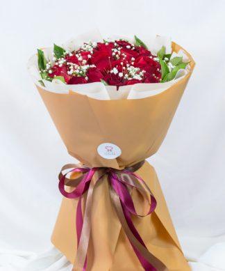 ช่อดอกกุหลาบแดงขนาดกลางจำนวน 20 ดอก ห่อด้วยกระดาษสีน้ำตาล