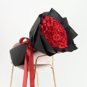 ช่อกุหลาบสีแดงสด 100 ดอกช่อใหญ่ ห่อด้วยกระดาษสีดำ ผูกริบบิ้นสีแดง