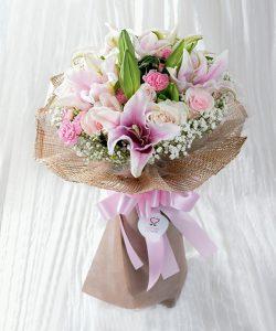 ช่อดอกไม้สดจัดด้วยดอกไม้โทนสีชมพู