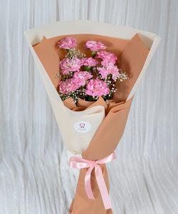 ช่อดอกคาร์เนชันสีชมพูอ่อน ห่อด้วยกระดาษสีเอิร์ธโทน