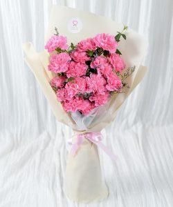 ช่อดอกคาร์เนชันสีชมพูสด ห่อด้วยกระดาษสีขาวครีม