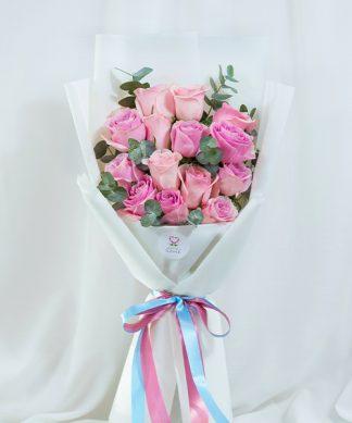 ดอกกุหลาบสีชมพูเข้มและชมพูอ่อน ห่อด้วยกระดาษสีขาว จัดเป็นทรงสูง