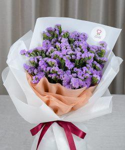 ช่อดอกไม้สด จัดด้วยดอกสแตติสสีม่วงทั้งช่อ ผูกริบบิ้นสีไวน์แดง