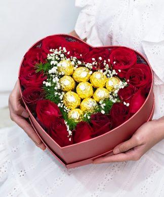 ดอกกุหลาบสีแดงในกล่องดอกไม้รูปหัวใจ พร้อมช็อกโกแลตเฟอเรโร่