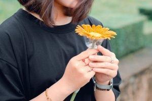 ผู้หญิงใส่เสื้อสีดำถือดอกเยอบีร่าสีส้มหนึ่งดอกไว้ในมือ