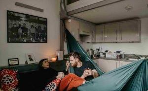 คู่รักชายหญิง ผู้หญิงนั่งโซฟา ผู้ชายนั่งในเปลผ้า