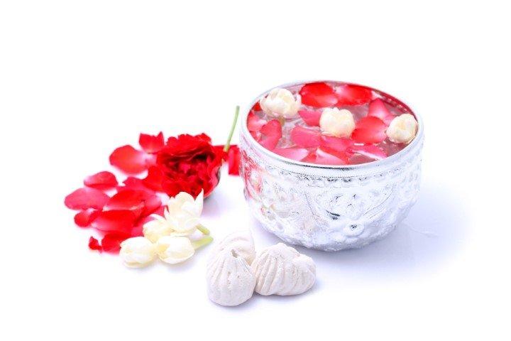ขันที่มีน้ำพร้อมดอกกุหลายและดอกมะลิลอยด้านบน