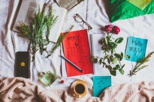 ดอกไม้วางอยู่บนโต๊ะที่มีปฏิทิน สมุด และแก้วกาแฟ