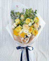 ช่อดอกไม้โทนสีเหลือง จัดด้วยดอกไม้หลายชนิด ผูกริบบิ้นสีน้ำเงิน