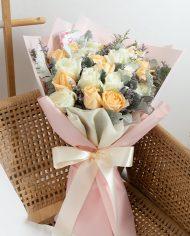 ช่อดอกกุหลาบสีขาวและดอกกุหลาบส้ม ผูกริบบิ้นที่ช่ออย่างสวยงาม