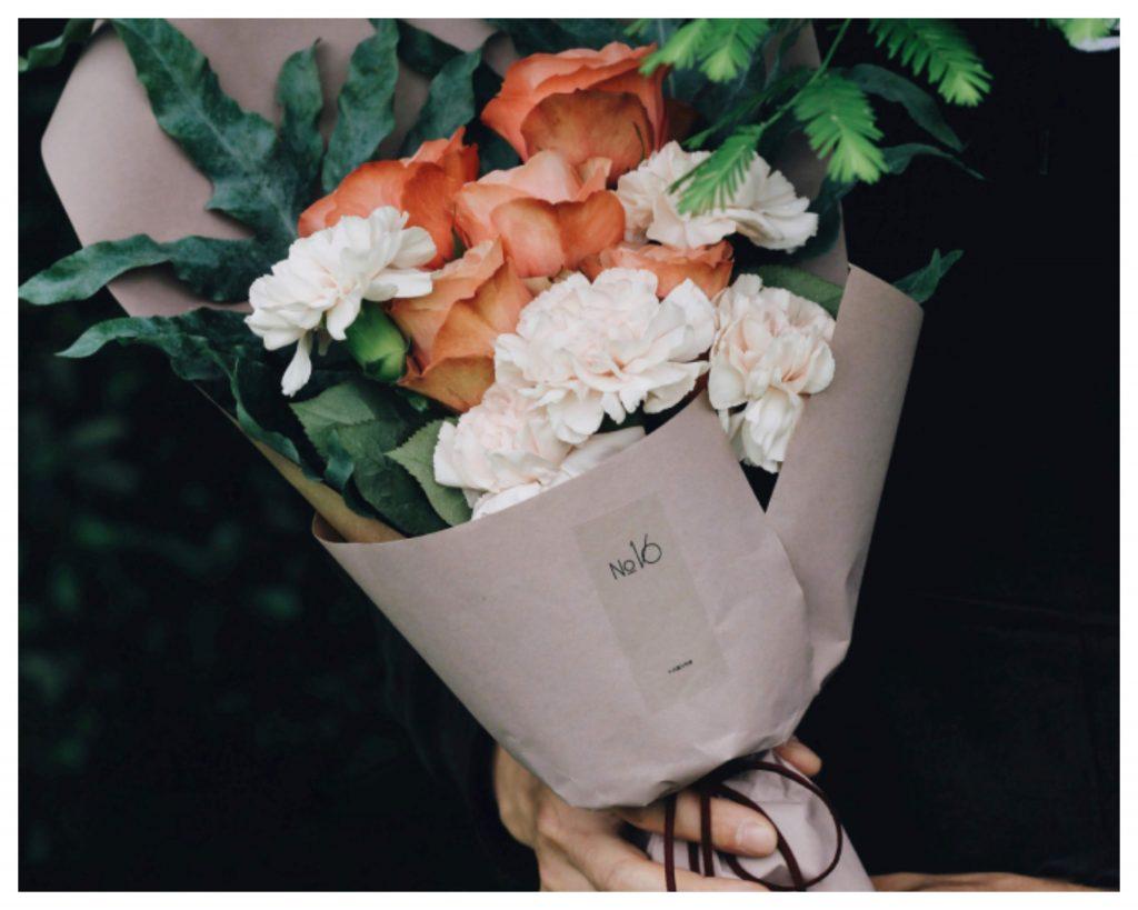 ช่อดอกไม้จัดด้วยดอกกุหลาบสีส้มและดอกคาร์เนชั่นสีขาว